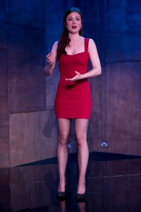 Female actor stood on stage wearing a modern red dress