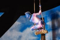 Actor with painted blue face wearing leotard and leggings crouched on a wooden swing