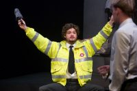 Actor dressed in London Underground hi viz jacket sat down with both arms outstretched and holding a folded up umbrella in his right hand, male actor to his right out of focus