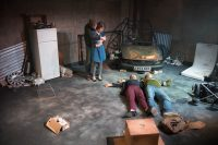 Actors on stage surrounded by debris