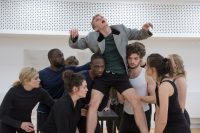 Students in rehearsals in the Weston Studio, all gathered together and lifting one of them above their heads