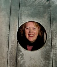 Headshot of Jill Blundell looking through a porthole in some wood