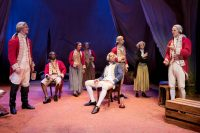 Actors sat and stood on stage dressed in old fashionned uniform