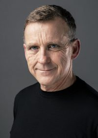 Headshot of man looking directly at camera in long sleeve black top