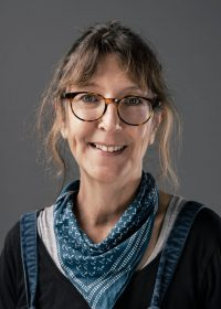 Headshot of a woman smiling with her hair in a ponytail, glasses and a blue scarf around her neck
