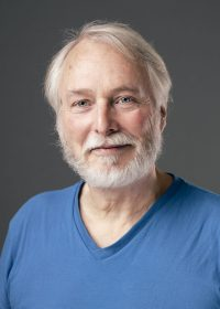 Headshot of man with grey hair and full beard in a blue top, looking at the camera directly