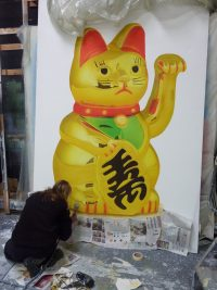 Scenic Art student completing a spray project of a chinese waving cat