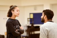 Female and male actors stood facing each other in rehearsals