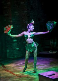 Actress stood with arms outstretched wearing a bikini top, and lace tights with leaf adornment