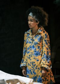 Actress stood on own wearing a yellow and blue floral dress and headband