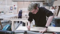 Male scenic art student marking wood in workshop