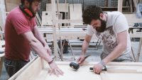 Two students constructing wooden pieces, one holding a hammer