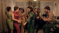 Actors in a living room set dressed in 60s clothing, dancing
