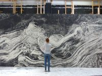 A scenic art student standing in front of a backdrop made for the Tempest