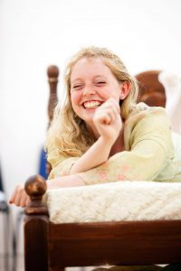 Female led on bed smiling