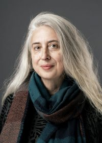 Headshot of lady with long grey hair looking directly at camera