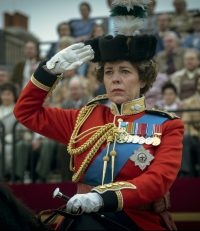 Olivia Colman in red military dress on a horse, saluting