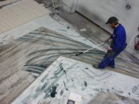 Scenic Art student painting the floor for the Wizard of Oz