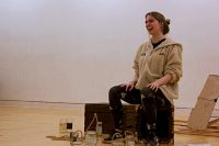 Student in rehearsal sat on box laughing