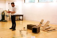 Student in rehearsal studio surrounded by boxes, jars and cardboard