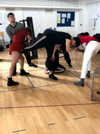 Students bent over in rehearsal