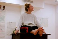 Student in rehearsal sat on desk laughing with no shoes on