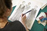 Close up of student holding pen and a drawing of costumes