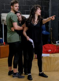 Three students in rehearsal, two holding each other and one pointing