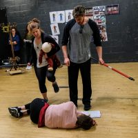 Two students kicking another student who is on the ground in rehearsal