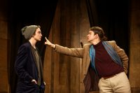 Two actors on stage, one pointing their finger at the other