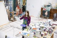 Artists stood surrounded by lots of paint pots