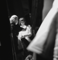 Black and white photo of female being dressed by dresser, reflection in mirror