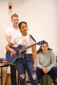 Students in rehearsal room, one stood holding a guitar