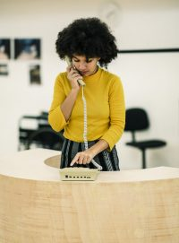 Acting student in rehearsal, stood behind a desk, speaking on a phone