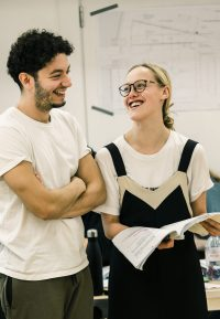 Two acting students in rehearsals, one holding a script