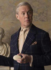 Still of Alex Jennings as Edward VIII stood up holding a bar of Floris soap