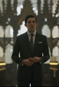 Josh O'Connor stood inside cathedral wearing a suit and tie