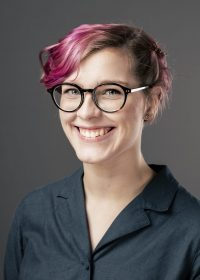 Headshot of female student with cropped pink hair and glasses, smiling at the camera