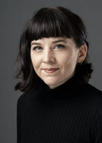 headshot of woman with short black hair and a full fringe in a black top