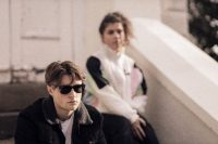 Show image for North of Providence: man with sunglasses and woman sitting in the background, 80s style