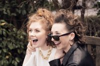 Show image for Dolores: two girls smiling, styled with 80s clothes and hair