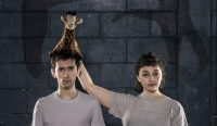Show image: A man and a woman in grey t shirts with blank expressions and a giraffe plush toy on the man's head