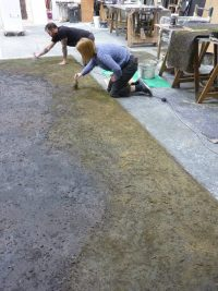 Artists knelt down painting floor