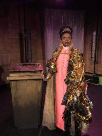 Actress wearing tiara and gold coat
