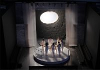 Model of figurines around a circular table with white light shining upon them