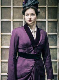 Actress wearing purple Edwardian jacket and skirt
