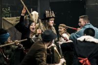 Action shot of various actors performing a scene from Macbeth, surrounding a figures in a crown