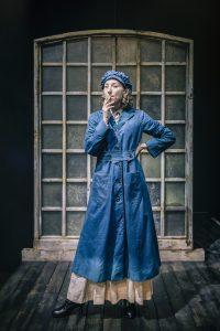 Actress in blue workwear, smoking