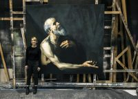 Photo of scenic artist posing by portrait of old man in robe with beard