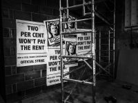 Black and white image of posters on a wall with pictures of Maggie Thatcher and scaffolding in front